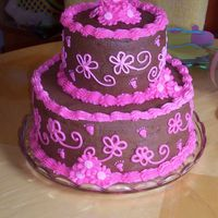 "Pink And Brown Baby Shower Cake I used 2- 10"" and 2- 6"" marble cake with Choc. Buttercream icing with pink buttercream details and some daisy's made w/..."