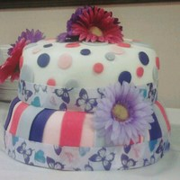 Dots & Stripes WASC cake with buttercream and raspberry filling covered in fondant--stripes and polka dots. Accented with a colorful daisies and butterfly...