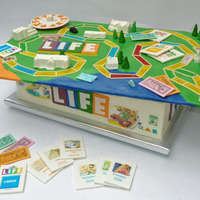 The Game Of Life - To Celebrate An Engagement The box is a BCF cake. The game board is a cake board covered with MMF and MMF details, candy melt cast buildings, and a gumpaste/MMF blend...
