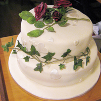 Wedding Cake With Roses White wedding cake with dark red roses and ivy
