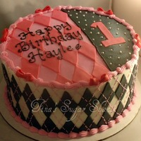 "Pink And Black Argyle 10"" round iced in buttercream with fondant accents. TFL"