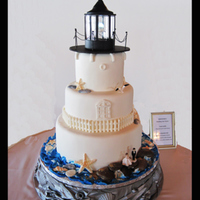 Lighthouse Wedding Cake I made the stand out of crinkled paper, glue and seashells then spray painted it silver. Shells and fence on the cake are white chocolate....