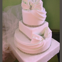 Bows And Bling Wedding Cake Gumpaste bows and drapes accented with rhinestone ribbons.