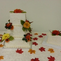 Fall Flowers 3 tier white cake french vanilla buttercream icing with hand piped scrolls and fall colored flowers. The small square cake was the 1st year...