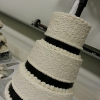 Elegant 3 tier white cake with french vanilla buttercream, black ribbon, and hand piped scrolls. They all loved it ;)