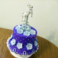 "Pretty Horse 8 and 10"" cakes iced in buttercream. On the 8"" I used a diamond press and attached dragees. The horseshoes,horse and flowers are..."