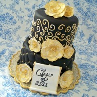 "Black And Gold 6 and 8"" cake covered in fondant. Flowers are gumpaste with sugar pearl centers and brushed with gold luster dust."