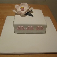 Pink Magnolia Cake - 50Th Birthday  Fondant covered square cake, decorated with a pink magnolia dusted in pink lustre dust. Design on the side of the cake was done using a...