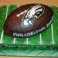 Eagles Football Cake Done for a BIG Eagles fan! The football cake is placed on a 1/2 sheet cake. sides decorated with chocolate footballs. Stitching, logo on...