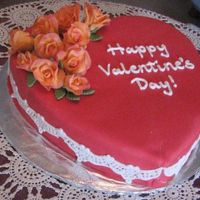 Red Heart Fondant orange roses tinged with pink. Chocolate cake covered in fondant. Fondant lace.
