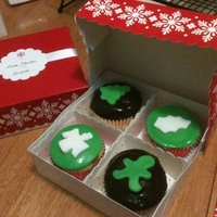 Christmas Cupcakes Made these for my kids' teachers. Green is poured fondant with a fondant cut out. Brown is chocolate ganache with a fondant cut out.