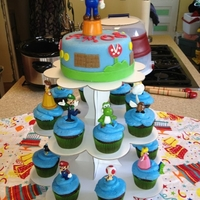 Nintendo Birthday Cake Cake for a 7th birthday. Top is MMF with a topper. Cupcakes are buttercream with cake toppers.