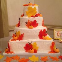 Fall Themed Wedding Cake Fall leaves and pumpkins made from fondant, cake iced in buttercream