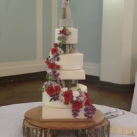 Woodsy Wedding Cake Roses, hydrangea, and wisteria all handmade from gumpaste. The separator stumps are also made of gumpaste and textured to look like the...