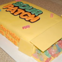 Sour Patch Cake   9 x 13 cake with buttercream and mmf. sour patch candies coming out of the box. flaps are gumpaste/fondant mix.