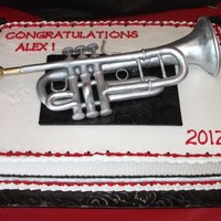 Trumpet Player's Graduation Cake Gumpaste/fondant trumpet painted with silver luster dust. The bell of the trumpet is a rice krispie treat covered in fondant.
