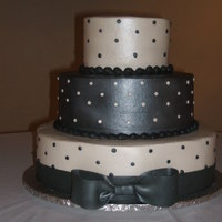 "Nancy All buttercream with MMF ribbon and bow. Sprayed with pearl luster. 12, 9, 6""."