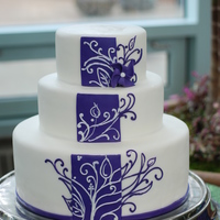 Purple Stripe 14,10,7. covered with white fondant, purple stripe down middle, bottom band, and pinwheel are all fondant.