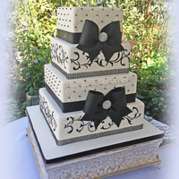 Black Bows And Broaches Wedding Cake  This is one of my favorite cakes that I've made. Fondant bows, ribbon and even the broach in the center of the bows is fondant....