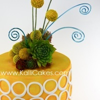 Modern Yet Earthy Real flowers adorn this fondant cake. Handpainted egg yellow with white fondant cutout circles which are purposefully not perfect to give a...
