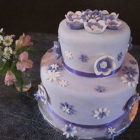 Purple Shower Cake Vanilla Cake with Vanilla Custard and Butter cream frosting covered in MMF with MMF Flowers and Purple Ribbon.