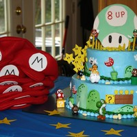 Mario Birthday Cake topper is made from gumpaste. Cake is iced with buttercream and decorations on cake are fondant and store bought figures.