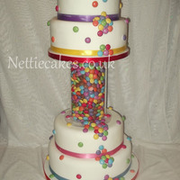 Smarties Wedding Cake this was great fun to design i used 26 tubes of smarties and got the ribbons to colour match the smarties.