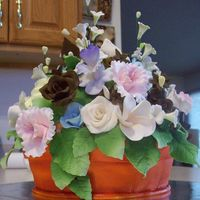 Flower Arrangement Cake Flowers are gumpaste and RI. Pot is chocolate covered in fondant and airbrushed terra cotta. Thanks for looking.