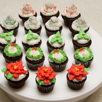 Mini Christmas Cupcakes Chocolate mini cupcakes with buttercream icing with poinsettias, wreaths, holly and berries, and sprinkles