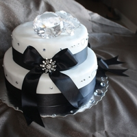 All About The Bling... A lemon cake with raspberry IMBC in the centre. Covered in fondant with black ribbon and glass diamonds to decorate
