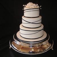 Elegant Ribbon Cake Elegant cake with black ribbon as the main contrast to the white fondant and white roses on top