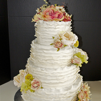 Fondant Ruffle Wedding Cake Ivory Fondant ruffles with fresh flowers.
