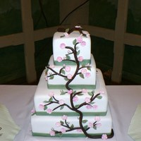 Cherry Blossom Cake this is a fondant covered cake covered with handmade blossoms and branches