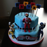 Multi Power Ranger Cake yellow blue and red power rangers all made out of fondant.