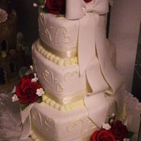 Hearts Of Love  3 tier heart shaped wedding cake is covered in a soft ivory colored fondant. Adorned with contrasting ivory hearts, soft ivory bows and...