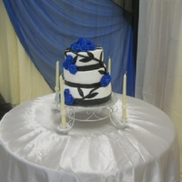 Blue Rose bc frosting, blue roses are made with royal icing, trim is made of mm fondant and leaves.