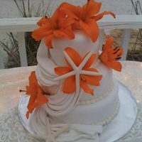 Beach Theme Round Wedding Cake Fondant with a swag and fresh flowers & dried star fish