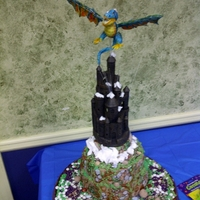 "Blu Nadder ""how to train a dragon"" cake. Nadder is modelling chocolate suspended over castle by clear poly rod. Fiber optic lights protrude..."