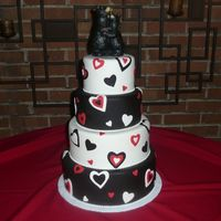 Bears In Love This is a fondant cake with fondant heart cut outs in black, white, and red. It is topped with two wodden black bears.