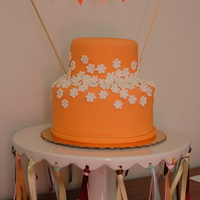 Orange Floral Cake Orange SatinIce fondant with Satinice gum paste daisies. Paper bunting reads MELISSA.