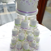 Lilac And Spring Green Blossom Wedding Cake  A top cutting tier covered with cascading blossom flowers and an abundance of individual cakes decorated with organza ribbon and a single...