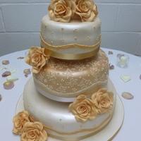 Golden Rose And Vintage Lace Wedding Cake   A beautiful three tier cake decorated with golden sugar roses and a piped lace design on the middle tier