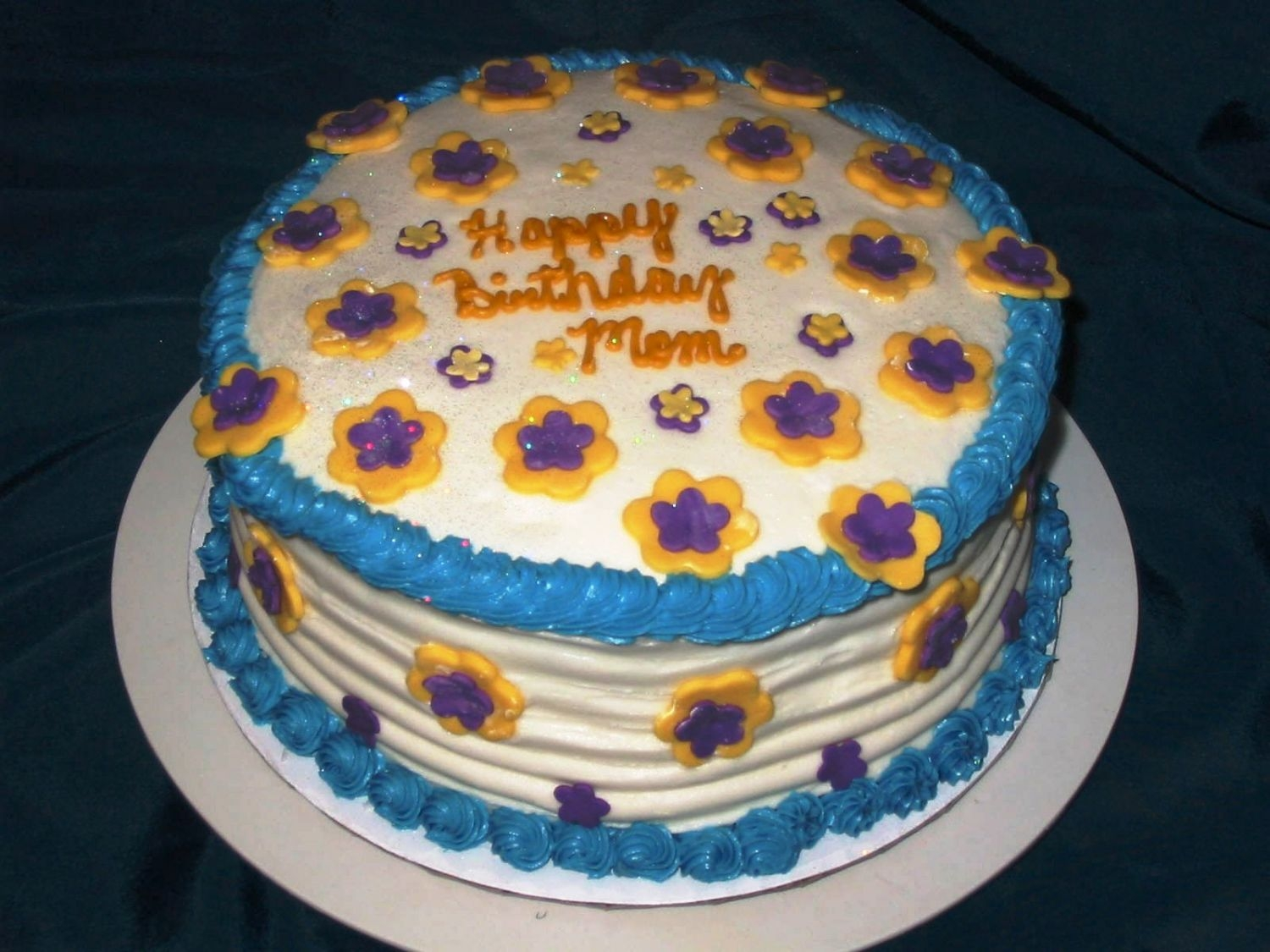 "Yellow & Purple Flower Cake This 8"" red velvet cake was iced in a crusting cream cheese icing with fondant flowers adoring it."