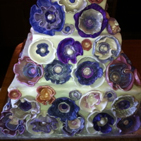 Purple Wedding Cake   This is a square version of a cake I had done in round layers. Flowers are fondant painted with luster dust.