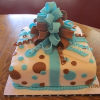 Present Cake Blue present cake with blue and brown circles with fondant bow.