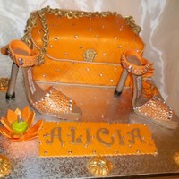 Orange Bling Cake for my girlfriend who loves bling and the color orange. Purse is lemon cake with edible bling. Gumpaste heels and chain.