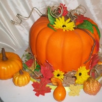 Fall Harvest Pumpkin Pumpkin is made with bundt pans. Cakes are Choc/Lemon. Fondant covering. Gumpaste leaves and flowers. Small pumpkin and goards are RKT.
