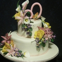 Lisa's Garden  birthday cake to celebrate a 60th birthday, purple fantasy flowers, roses, calla lilies, and violet stephanotis like flowers. Ivory fondant...