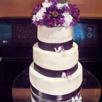 Purple Wedding Cake   German Chocolate cake with buttercream . Dark purple ribbon border and silk flowers.
