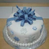 Snow Flake And Bow Cake This is a white cake covered in fondant and decorated with fondant snow flakes and a fondant ribbon. Snow flakes are blue and silver